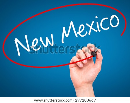 Man Hand writing New Mexico with black marker on visual screen. Isolated on blue. Business, technology, internet concept. Stock Photo - stock photo