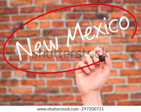 Man Hand writing New Mexico with black marker on visual screen. Isolated on bricks. Business, technology, internet concept. Stock Photo - stock photo