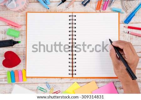Man hand writing  Notebook paper and school or office tools on vintage wood table for text and background.copy space