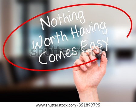 Man Hand writing Nothing Worth Having Comes Easy with black marker on visual screen. Isolated on background. Business, technology, internet concept. Stock Photo - stock photo