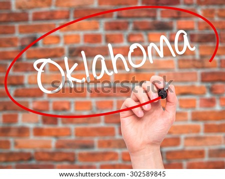 Man Hand writing Oklahoma with black marker on visual screen. Isolated on bricks. Business, technology, internet concept.  - stock photo