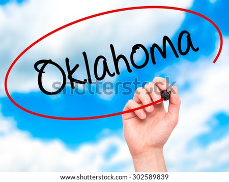 Man Hand writing Oklahoma with black marker on visual screen. Isolated on sky. Business, technology, internet concept.  - stock photo