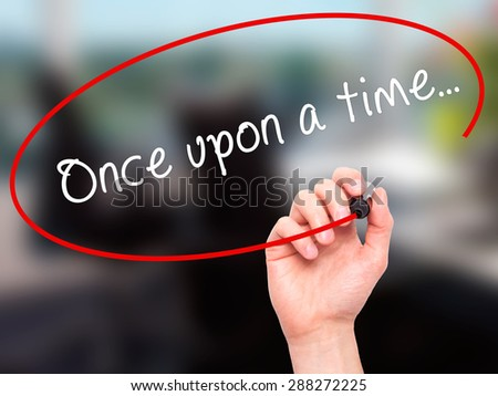 Man Hand writing Once upon a time... with black marker on visual screen. Isolated on office. Business, technology, internet concept. Stock Image - stock photo