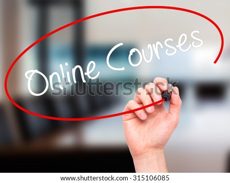 Man Hand writing Online Courses with black marker on visual screen. Isolated on office. Business, technology, internet concept. Stock Photo - stock photo