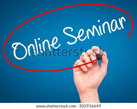 Man Hand writing Online Seminar with black marker on visual screen. Isolated on blue. Business, technology, internet concept. Stock Photo - stock photo