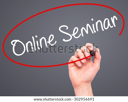 Man Hand writing Online Seminar with black marker on visual screen. Isolated on grey. Business, technology, internet concept. Stock Photo - stock photo