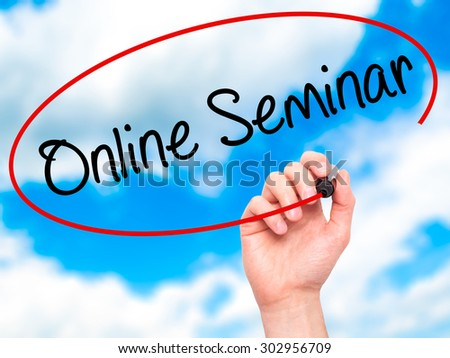 Man Hand writing Online Seminar with black marker on visual screen. Isolated on sky. Business, technology, internet concept. Stock Photo - stock photo