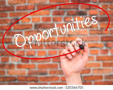Man Hand writing Opportunities  with black marker on visual screen. Isolated on bricks. Business, technology, internet concept. - stock photo
