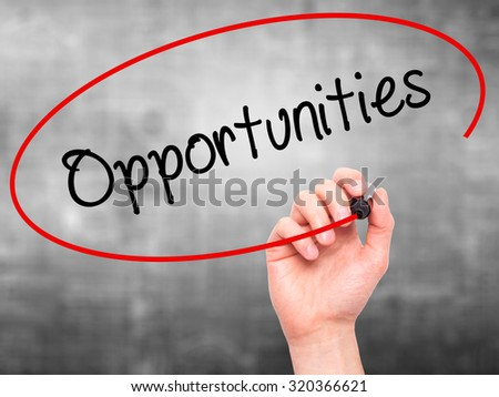 Man Hand writing Opportunities  with black marker on visual screen. Isolated on grey. Business, technology, internet concept. - stock photo