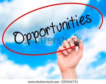 Man Hand writing Opportunities  with black marker on visual screen. Isolated on sky. Business, technology, internet concept. - stock photo