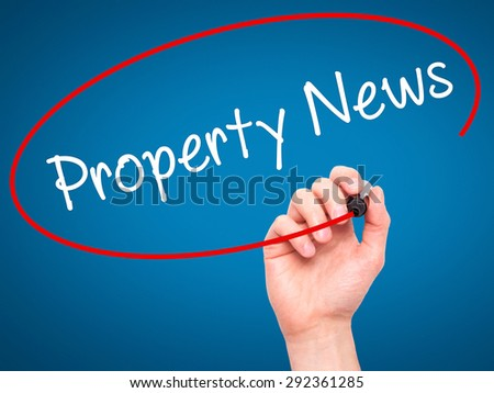 Man Hand writing Property News with black marker on visual screen. Isolated on blue. Business, technology, internet concept. Stock Image - stock photo