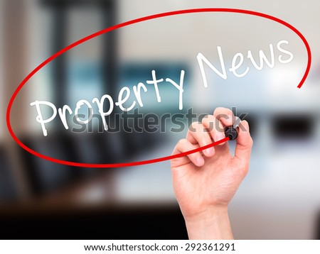 Man Hand writing Property News with black marker on visual screen. Isolated on office. Business, technology, internet concept. Stock Image - stock photo