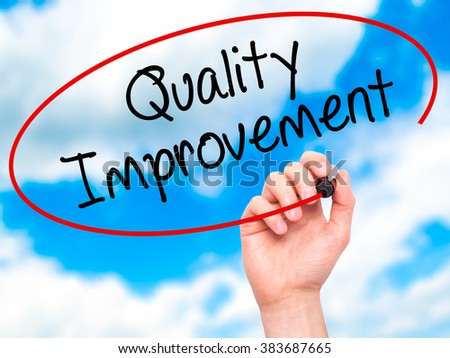 Man Hand writing Quality Improvement with black marker on visual screen. Isolated on background. Business, technology, internet concept. Stock Photo - stock photo
