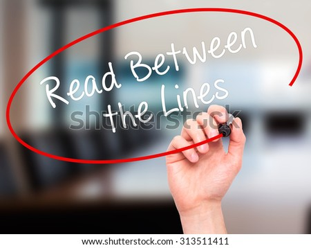 Man Hand writing Read Between the Lines   with black marker on visual screen. Isolated on office. Business, technology, internet concept. Stock Photo - stock photo