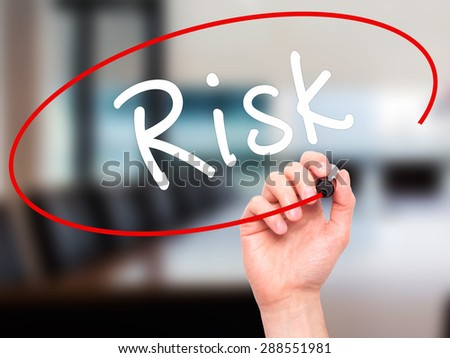 Man Hand writing Risk with black marker on visual screen. Isolated on office. Business, technology, internet concept. Stock Image - stock photo