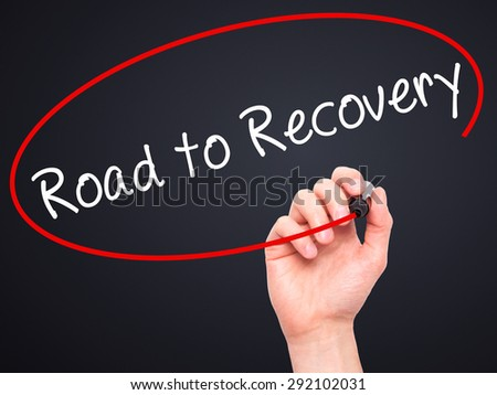 Man Hand writing Road to Recovery with black marker on visual screen. Isolated on black. Business, technology, internet concept. Stock Image - stock photo