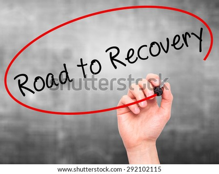 Man Hand writing Road to Recovery with black marker on visual screen. Isolated on grey. Business, technology, internet concept. Stock Image - stock photo