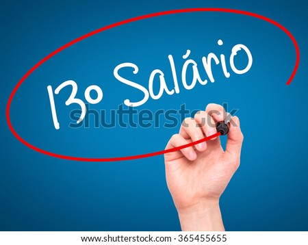 Man Hand writing 13 Salary (13º Salário In Portuguese)  with black marker on visual screen. Isolated on background. Business, technology, internet concept. Stock Photo - stock photo
