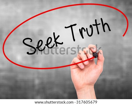 Man Hand writing Seek Truth with black marker on visual screen. Isolated on grey. Business, technology, internet concept. - stock photo