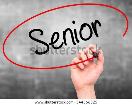 Man Hand writing Senior with black marker on visual screen. Isolated on background. Business, technology, internet concept. Stock Photo