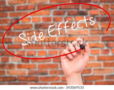 Man Hand writing Side Effects with black marker on visual screen. Isolated on bricks. Business, technology, internet concept. Stock Photo - stock photo