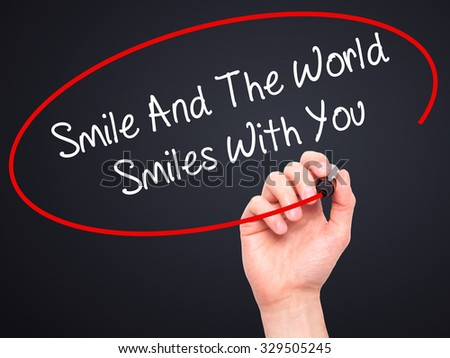 Man Hand writing Smile And The World Smiles To You with black marker on visual screen. Isolated on black. Business, technology, internet concept. Stock Photo