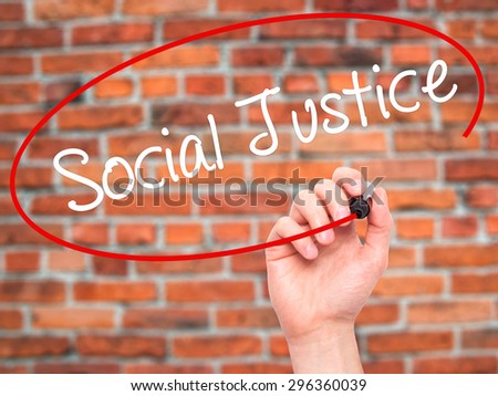 Man Hand writing Social Justice with black marker on visual screen. Isolated on bricks. Business, technology, internet concept. Stock Photo - stock photo