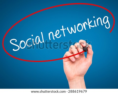 Man Hand writing Social networking with black marker on visual screen. Isolated on blue. Business, technology, internet concept. Stock Image - stock photo