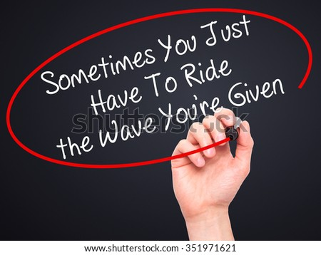 Man Hand writing Sometimes You Just Have To Ride the Wave You're Given with black marker on visual screen. Isolated on background. Business, technology, internet concept. Stock Photo