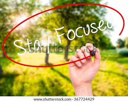Man Hand writing Stay Focused with black marker on visual screen. Isolated on background. Business,  technology, internet concept. Stock Photo - stock photo
