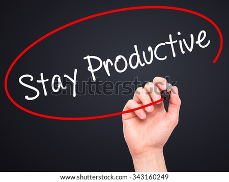 Man Hand writing Stay Productive with black marker on visual screen. Isolated on black. Business, technology, internet concept. Stock Photo - stock photo