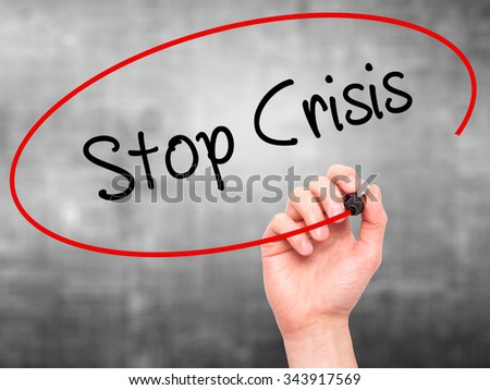 Man Hand writing Stop Crisis with black marker on visual screen. Isolated on background. Business, technology, internet concept. Stock Photo