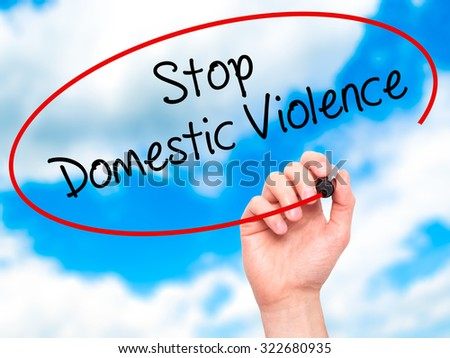 Man Hand writing  Stop Domestic Violence with black marker on visual screen. Isolated on sky. Business, technology, internet concept. Stock Photo - stock photo