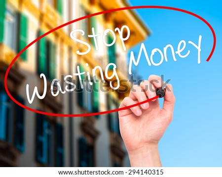 Man Hand writing Stop Wasting Money with black marker on visual screen. Isolated on city. Business, technology, internet concept. Stock Photo - stock photo