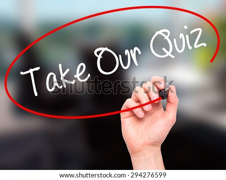 Man Hand writing Take Our Quiz with black marker on visual screen. Isolated on office. Business, technology, internet concept. Stock Photo - stock photo