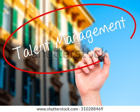 Man Hand writing Talent Management with black marker on visual screen. Isolated on city. Business, technology, internet concept. Stock Photo - stock photo