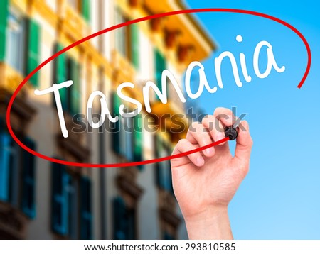 Man Hand writing Tasmania with black marker on visual screen. Isolated on city. Business, technology, internet concept. Stock Photo - stock photo