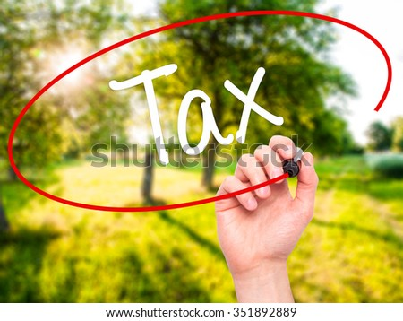 Man Hand writing Tax with black marker on visual screen. Isolated on background. Business, technology, internet concept. Stock Photo - stock photo