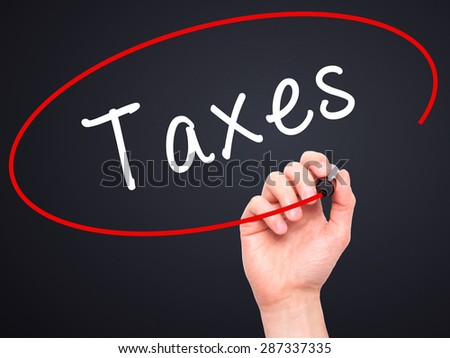 Man Hand writing Taxes with marker on transparent wipe board. Isolated on black. Business, internet, technology concept. Stock Photo - stock photo