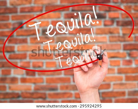 Man Hand writing Tequila with black marker on visual screen. Isolated on bricks. Business, technology, internet concept. Stock Photo - stock photo