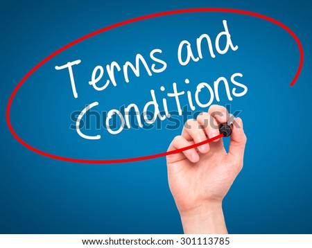 Man Hand writing Terms and Conditions with black marker on visual screen. Isolated on blue. Business, technology, internet concept. Stock Photo - stock photo