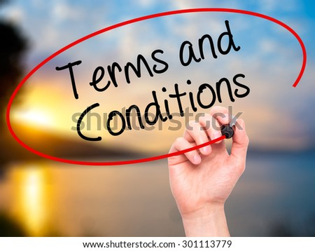 Man Hand writing Terms and Conditions with black marker on visual screen. Isolated on nature. Business, technology, internet concept. Stock Photo - stock photo