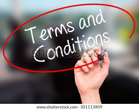 Man Hand writing Terms and Conditions with black marker on visual screen. Isolated on office. Business, technology, internet concept. Stock Photo - stock photo