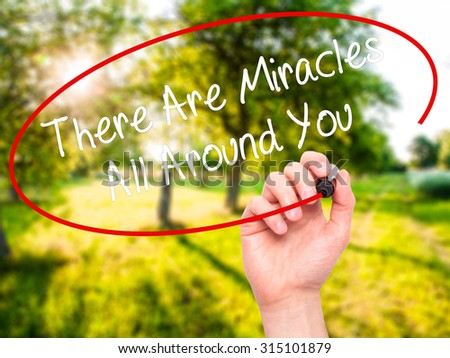 Man Hand writing There Are Miracles All Around You  with black marker on visual screen. Isolated on nature. Business, technology, internet concept. Stock Photo - stock photo