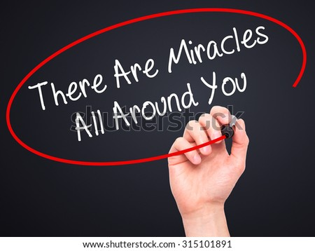 Man Hand writing There Are Miracles All Around You  with black marker on visual screen. Isolated on black. Business, technology, internet concept. Stock Photo - stock photo