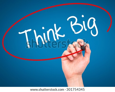 Man Hand writing Think Big with black marker on visual screen. Isolated on blue. Business, technology, internet concept. Stock Photo - stock photo