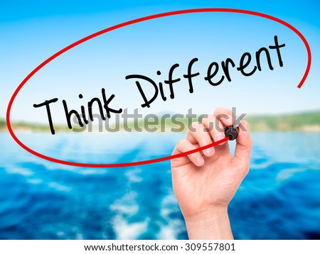 Man Hand writing Think Different with black marker on visual screen. Isolated on nature. Business, technology, internet concept. Stock Photo - stock photo