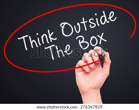 Man Hand writing Think Outside The Box with marker on transparent wipe board. Isolated on black. Business, internet, technology concept.  Stock Photo - stock photo