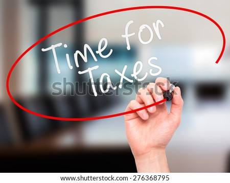 Man Hand writing Time for Taxes with marker on transparent wipe board. Isolated on office. Business, internet, technology concept.  Stock Photo - stock photo