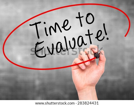 Man Hand writing Time to Evaluate with marker on transparent wipe board. Isolated on grey. Business, internet, technology concept. Stock Photo - stock photo